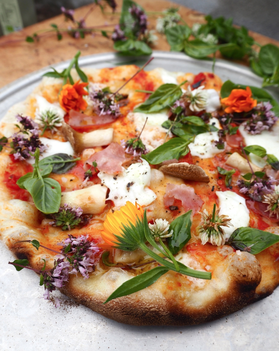 Homemade wood-fired pizza with herbs